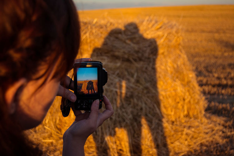 Woman photographing shadow of couple on hay during sunset