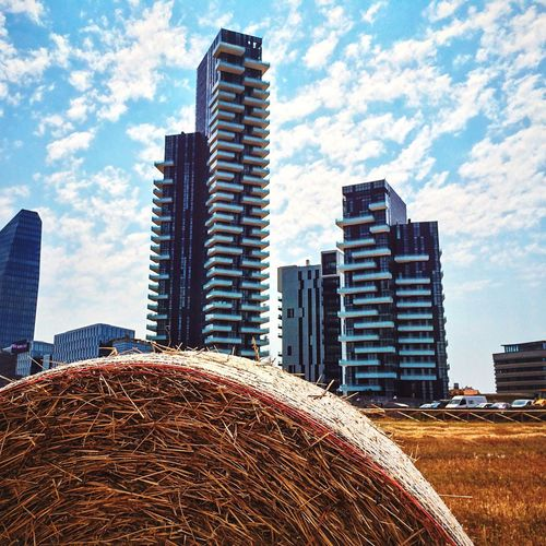 Close-up of hay bale in wheat field by skyscrapers against sky