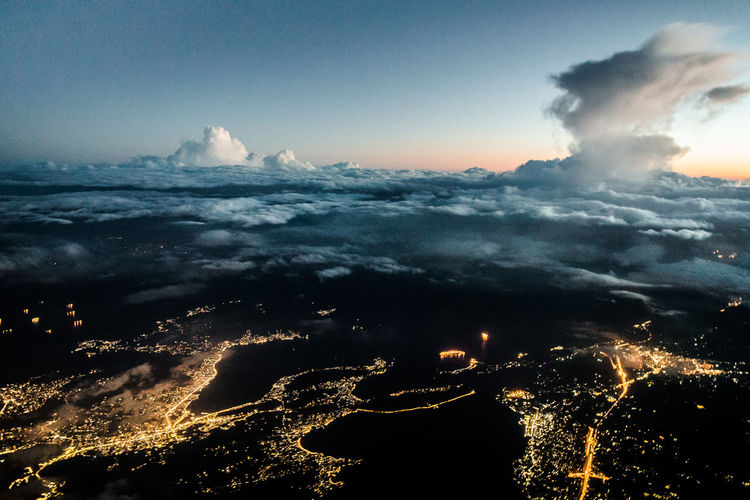 Aerial view of illuminated city against sky at sunset