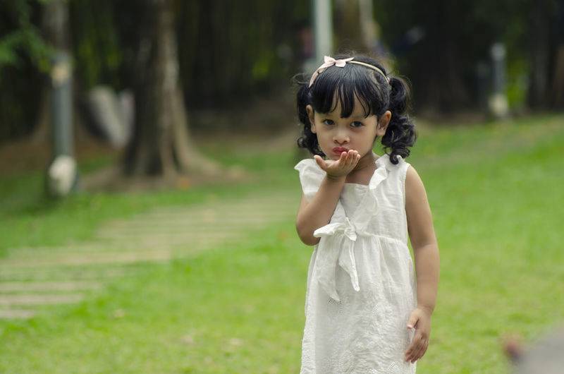 little cute girl giving flying kiss over shallow depth of field background Childhood Child One Person Standing Innocence Focus On Foreground Women Land Plant Girls Females Grass Day Looking At Camera Portrait Nature Tree Three Quarter Length Looking Outdoors Hairstyle Bangs
