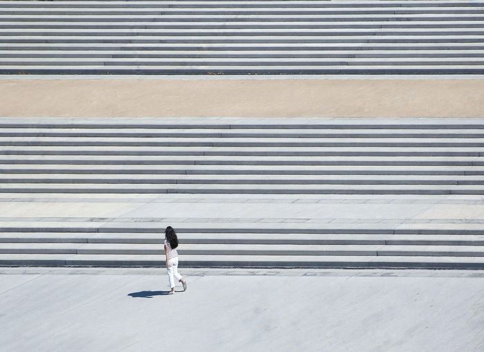 High angle view of woman walking by steps