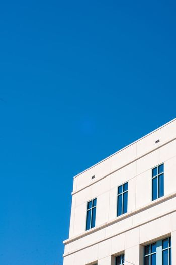 Low angle view of building against clear blue sky during sunny day