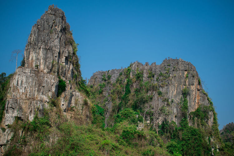Sky Rock Rock - Object Mountain Solid Clear Sky Nature Rock Formation Plant No People Tranquil Scene Day Tranquility Low Angle View Scenics - Nature Beauty In Nature Environment Blue Land Non-urban Scene Outdoors Formation Mountain Peak Eroded Semi-arid