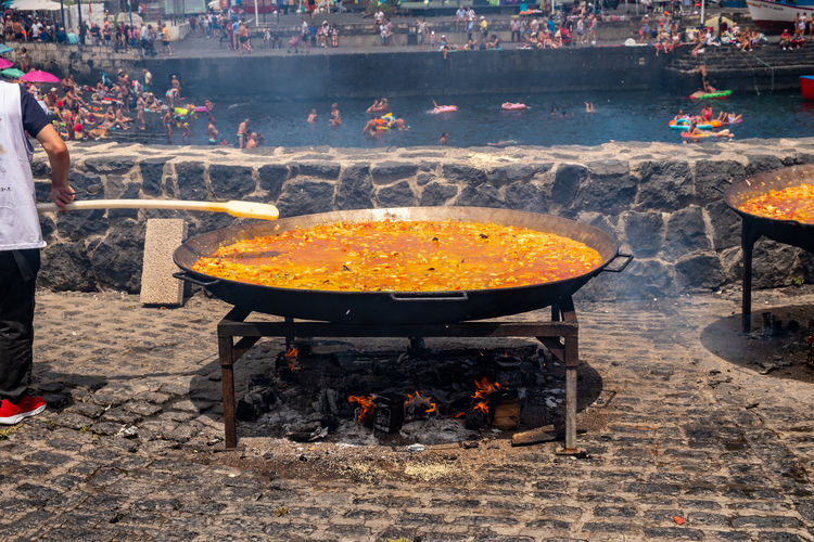 "Paella is common throughout Spain in a variety of variants and belongs to family life - this makes them the national dish. The ingredients of a paella can be completely different. But three ingredients are always the same, rice, saffron and olive oil. Really real is the preparation of the paella only outdoors in a large flat pan (Spanish ""Paellera""), and in a wood oven. Smoke is desirable because smoke adds to the flavor of the paella. Bonfire Cooking EyeEm Best Shots Harbor Hot Meal Paella Puerto De La Cruz Rice Seafood Smoke Barbecue Eye4photography  Fire Fire - Natural Phenomenon Flame Food Heat - Temperature Kitchen Pan Preparation  Saffron Tenerife Teneriffa Virgen Del Carmen"