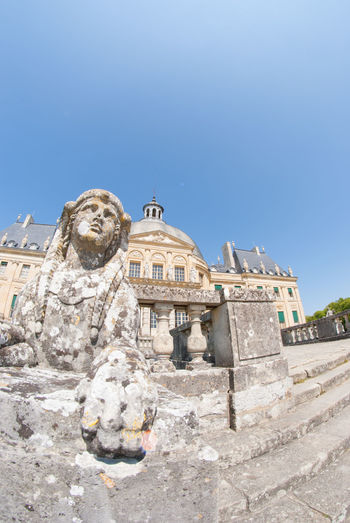 A Beautiful Rock Statue With The Chateau De Vaux Le Vicomte In The Background. The House Is A Baroque French Chateau Located In Maincy, Near Melun, 55 Km Southeast Of Paris Taken With Fisheye Lens. Architecture Beautiful Building Exterior Built Structure Château Clear Sky Day Europe France History History Architecture Holiday Low Angle View Maincy Melun No People Outdoors Paris Sculpture Statue Stone Material Structure Tourism Travel Destinations Vicomte