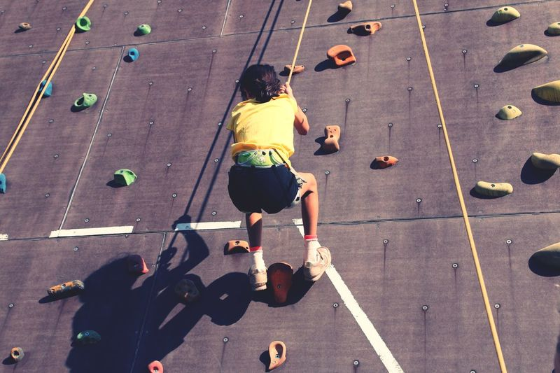 Low angle view of girl climbing on artificial wall
