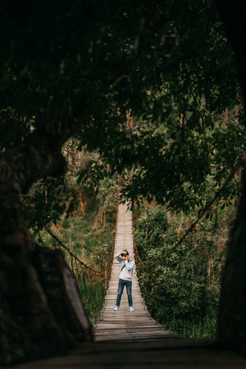 Man photographing while standing on rope bridge