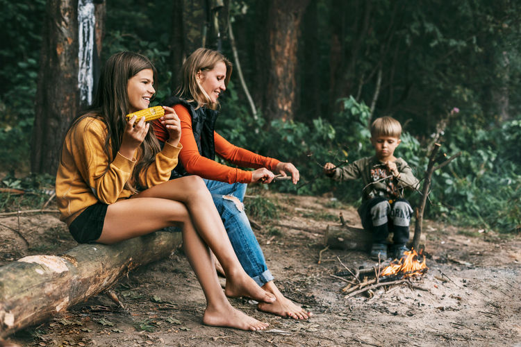 Siblings sitting on land in forest