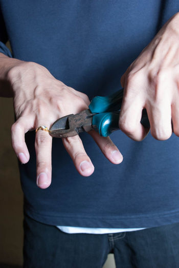 Midsection of man removing wedding ring with hand tool