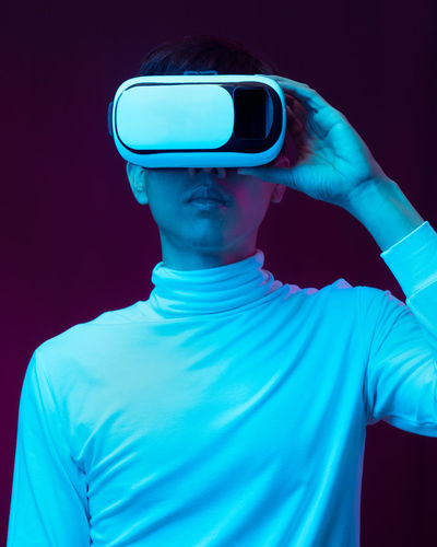 Young man using virtual reality simulator against colored background