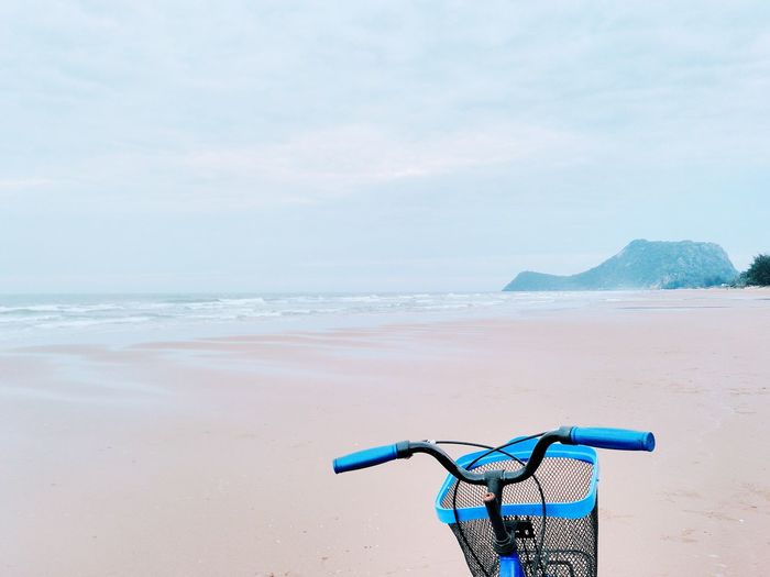 Blue bicycle at beach against sky