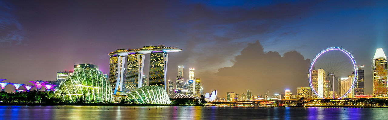 Panoramic view of Singapore skyline view of skyscrapers on Marina Bay at sunset Building Exterior Architecture Built Structure Night Sky Illuminated Water Waterfront City Reflection Nature Building No People Travel Destinations Office Building Exterior Skyscraper Cloud - Sky Tall - High Modern Financial District  Bay Singapore Marina Bay Sands Cityscape Asian  Panoramic Twilight Urban Sunset Iconic