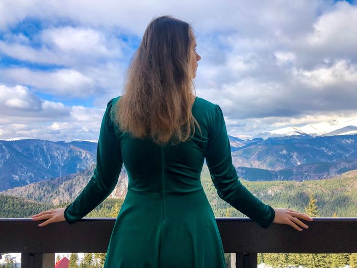 Rear view of woman standing in balcony against mountains