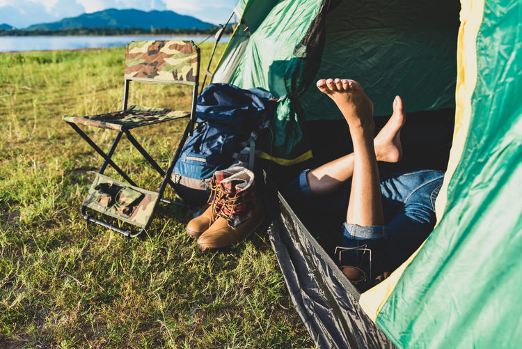 Close up of woman legs relaxing in camping tent with mountain lake and meadow and grass field background. Lifestyles and People concept. Camping and picnec theme. Green natural and summer travel theme Woman Body Part Camping Day Grass Human Foot Human Leg Human Limb Land Leisure Activity Lifestyles Low Section Lying Down Lying On Back Men Nature Outdoors People Real People Relaxation Resting Shorts Tent Trip Vacations The Photojournalist - 2018 EyeEm Awards