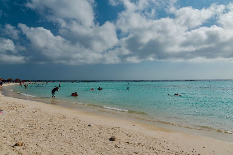 People swimming in sea against cloudy sky