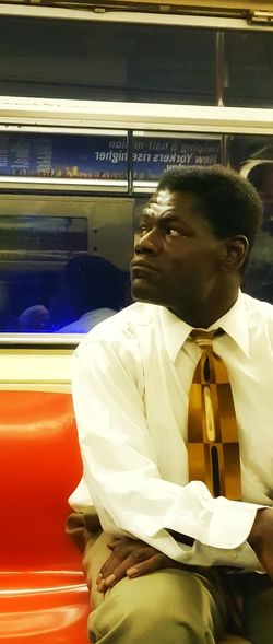 Young man looking away while traveling in train