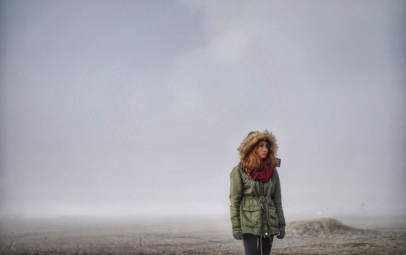 Woman looking away while standing on field during foggy weather