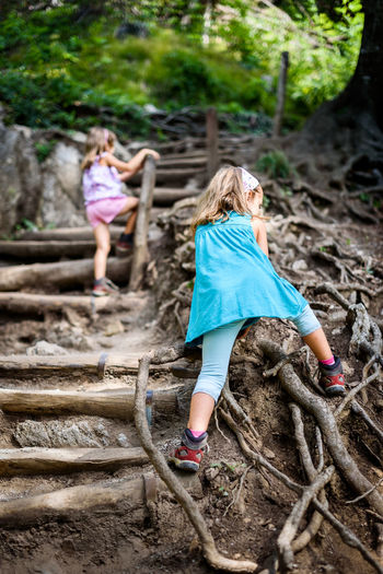 Low angle view of sisters climbing steps in forest