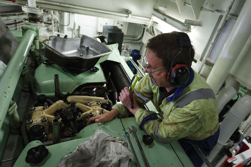 A Marine Engineer changing a fuel injector on an Offshore Supply Ship's marine diesel engine Engine Room Oil & Gas PPE Seafarer Engineer Expertise Indoors  Machinery Maintenance Work Mechanic Mode Of Transport Occupation One Person People Real People Skill  Technology Transportation Working