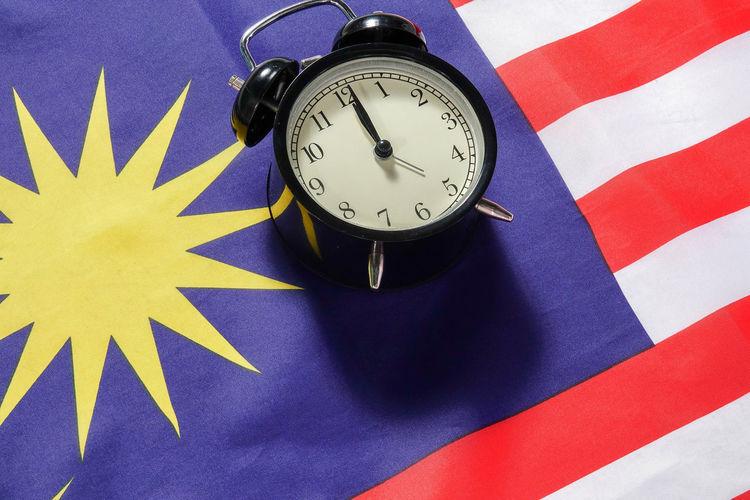 High angle view of alarm clock on malaysian flag