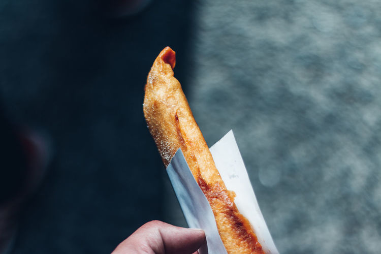Close-up of hand holding potato pie of  stick style that took away at street market