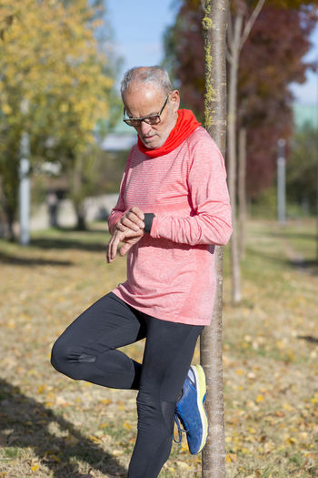Senior man outdoors stretching and monitoring after jogging Adult Day Exercising Focus On Foreground Glasses Healthy Lifestyle Leisure Activity Lifestyles Males  Mature Adult Mature Men One Person Outdoors Plant Real People Senior Adult Sport Tree