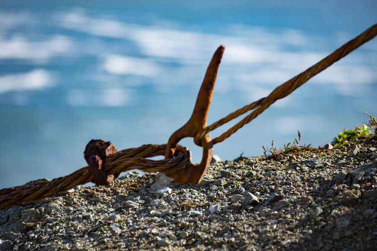 Rusted link holding cables together with water in the background. Corroded Links Metal No People Outdoors Rusty Selective Focus Tension