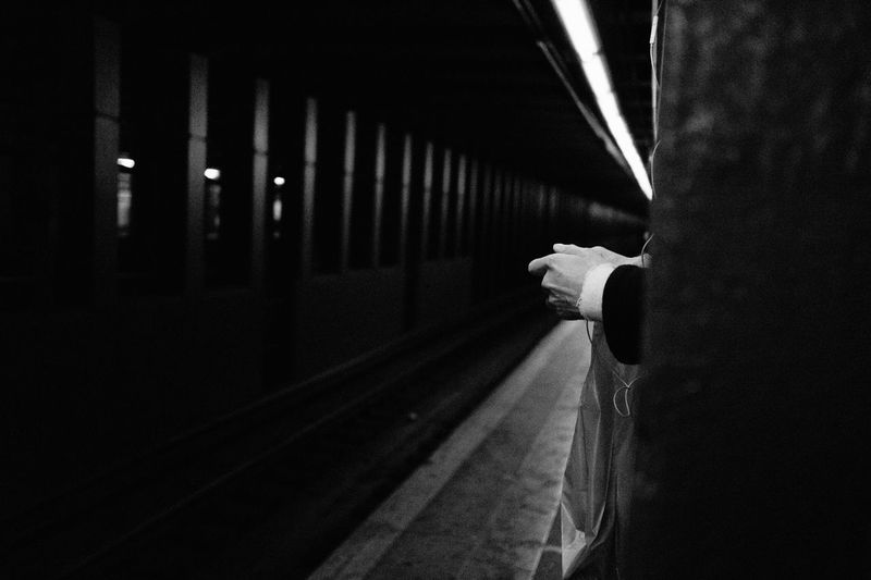 Cropped hand of person waiting on subway station platform