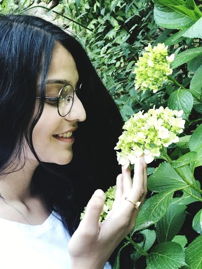 Smiling woman looking at white flowers