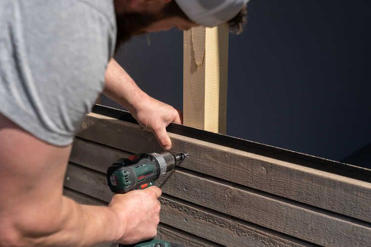 Midsection of man working against wall