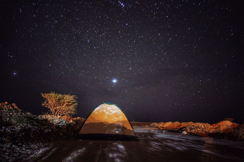 Tent on land against star field at night