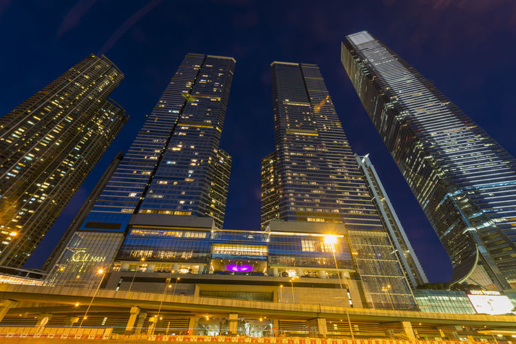 LOW ANGLE VIEW OF MODERN SKYSCRAPER AT NIGHT