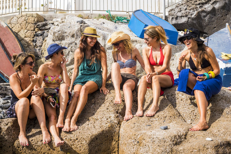 group of nice and beautiful friends smiling together having fun in friendship summer leisure time outdoor near the beach. swuimsuits and ladies enjoying the weather and the sun Group Of People Sitting Leisure Activity Friendship Togetherness Smiling Girls Child Day Nature People Fun Full Length Hat Adult Happiness Land Enjoyment Teenager Outdoors Adolescence  Teenage Boys Friends barefoot Six People Women Females Enjoying Life Bathsun Sea Rock Swimsuit Wather Tropical Caucasian Talking Confidence  Lifestyles Relaxation Positive Emotion Independence Bonding