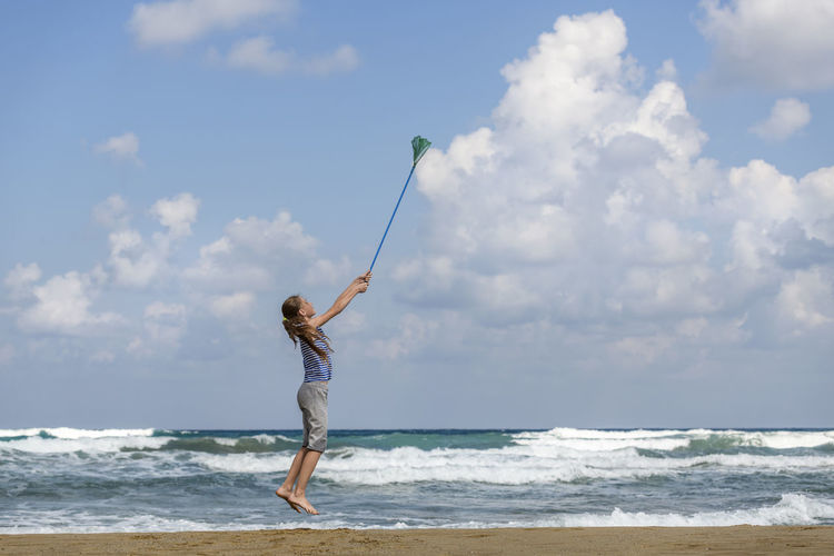 Full length of girl jumping with fishing net at beach against sky