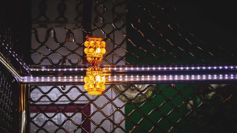 Illuminated chainlink fence against sky at night