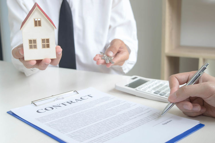 Midsection of real estate agent giving keys while client signing contract