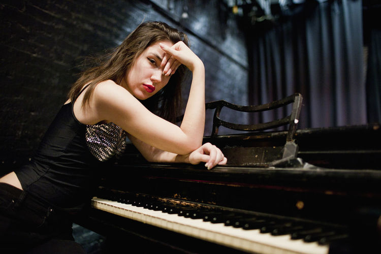 Full length of a young woman playing piano