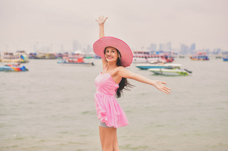 Arms Raised Beach Beautiful Woman Clothing Focus On Foreground Hairstyle Happiness Hat Human Arm Land Leisure Activity Lifestyles Limb One Person Pink Color Real People Sea Smiling Standing Sun Hat Water Women Young Adult Young Women