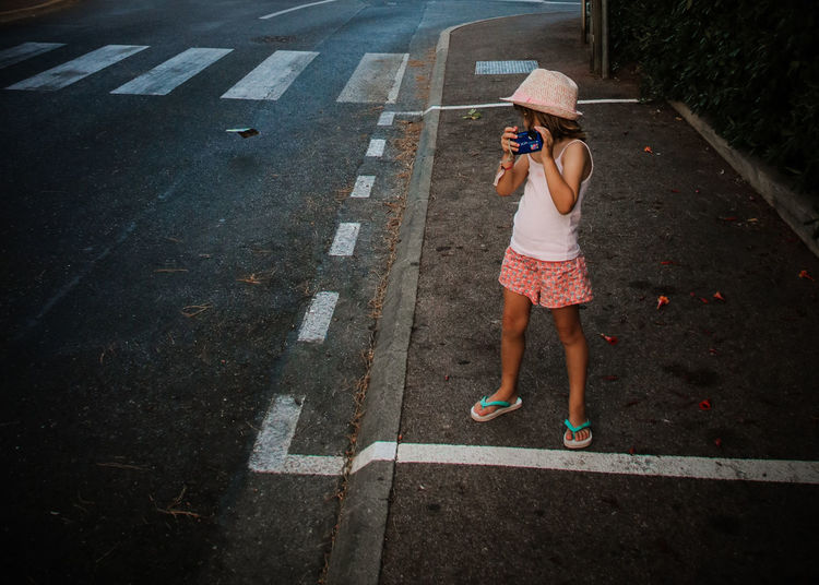 Girl With Camera Standing On Footpath