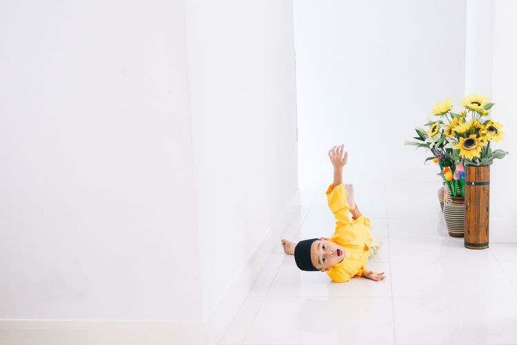 Boy In Traditional Clothing Lying On Floor