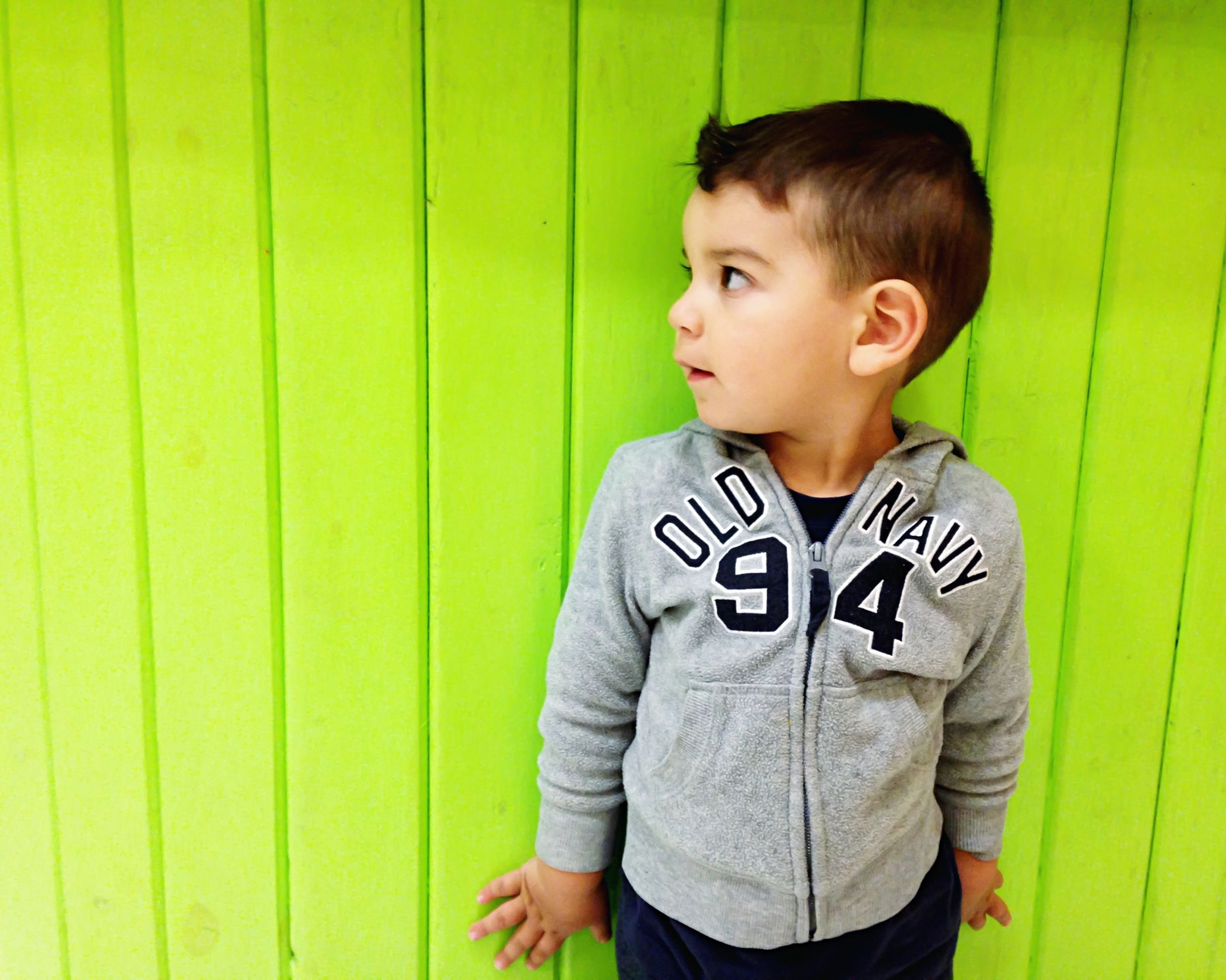 person, casual clothing, lifestyles, portrait, three quarter length, childhood, waist up, front view, standing, looking at camera, leisure activity, elementary age, boys, wall - building feature, smiling, innocence