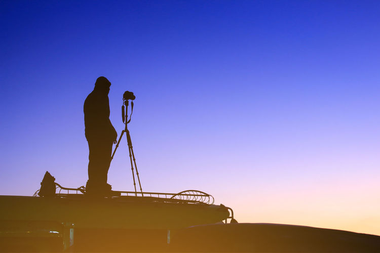 Side view of silhouette man photographing against clear sky during sunset