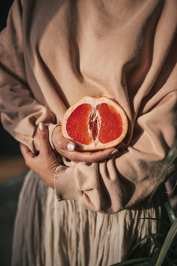 Midsection of woman holding fruit