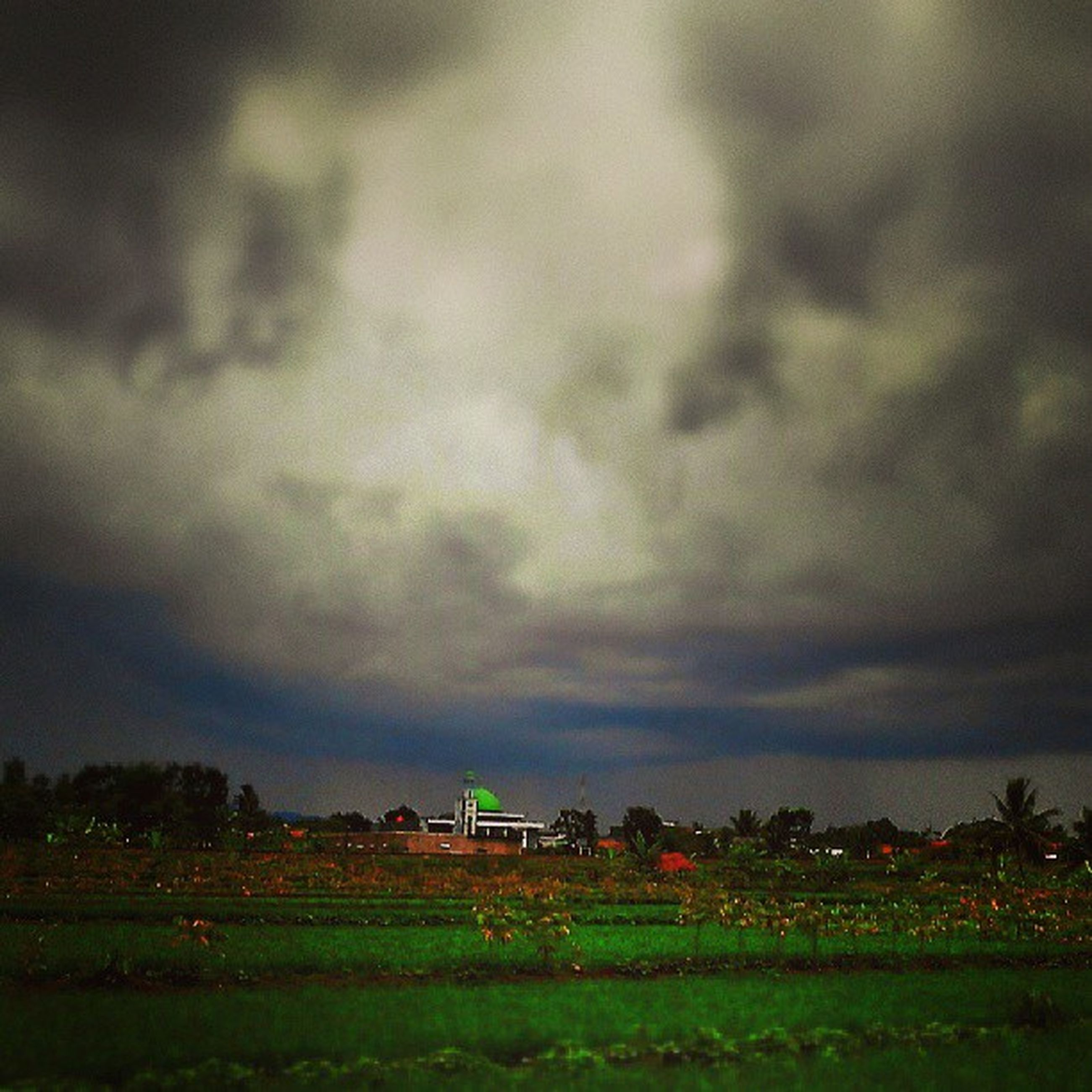 field, sky, landscape, building exterior, cloud - sky, cloudy, built structure, architecture, rural scene, weather, overcast, house, grass, storm cloud, agriculture, tranquil scene, nature, dusk, farm, tranquility
