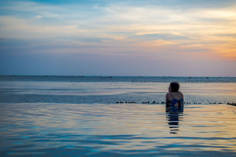 Rear View Of Woman In Swimming Pool On Beach Against Sky During Sunset