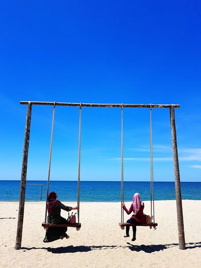 Rear view of women swinging at beach against sky on sunny day