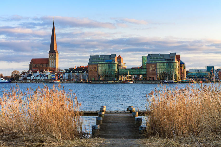 View over the river Warnow to the city Rostock, Germany. Church City Place Of Worship Relaxing Rostock Travel Architecture Building Exterior Built Structure Cloud - Sky Day Landing Stage Landmark Nature No People Outdoors Reeds River Sky Tourism Town Travel Destinations Vacation Warnow