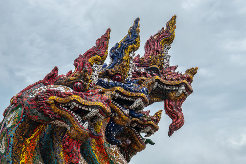 Low angle view of dragon statues against sky