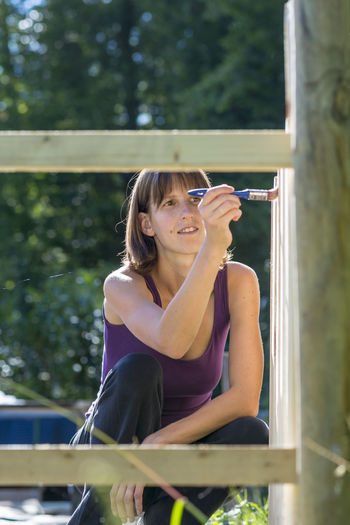 Portrait of a smiling young woman holding glass while sitting outdoors