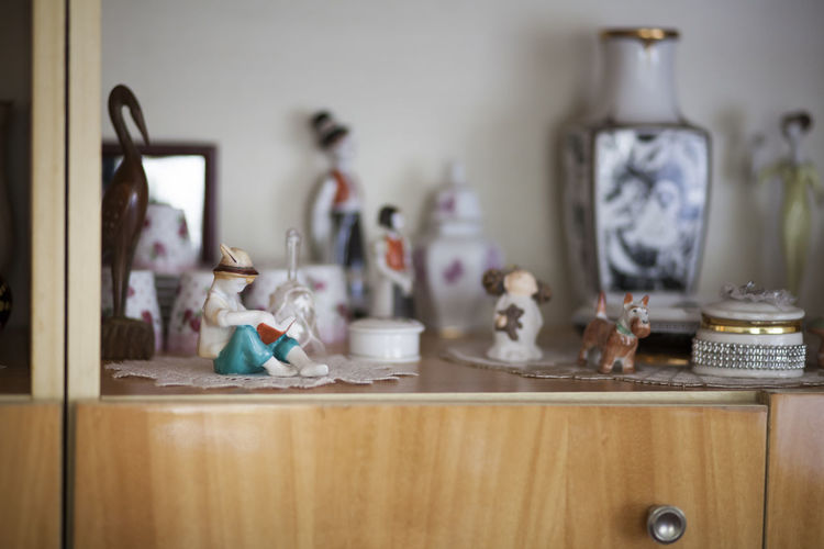 Close-Up Of Figurines On Showcase At Home